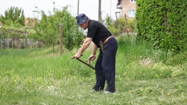 man mowing the grass. - scythe stock videos and b-roll footage