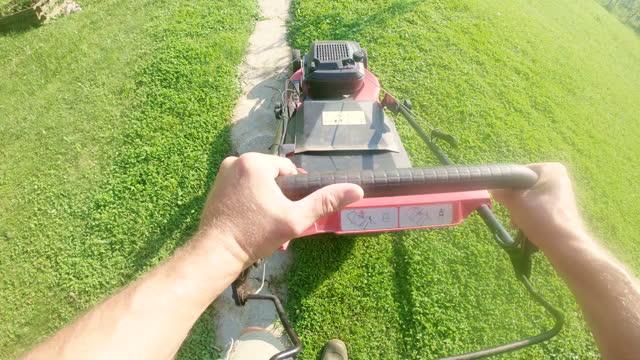 vidéos et rushes de homme de pov fauchant la pelouse dans l'arrière-cour - caméra portable