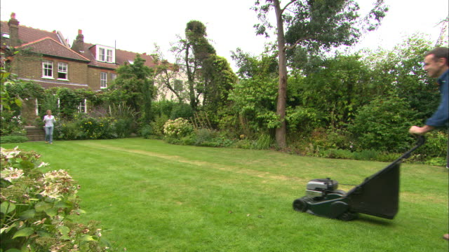 WS man mows lawn she approaches with tea