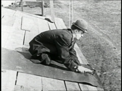 b/w 1924 man nailing tar paper onto roof / short - 1924 stock videos & royalty-free footage