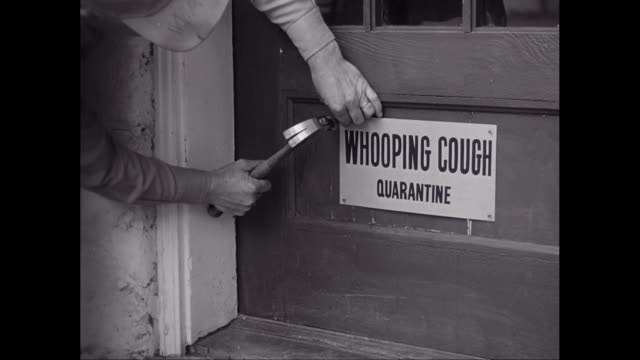 CU Man nailing Whooping cough sign on door / United States