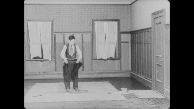 1920 man (buster keaton) nails a rug down to the floor, trapping his jacket underneath, so he cuts the jacket out and places a throw rug over the hole - reminder stock videos and b-roll footage