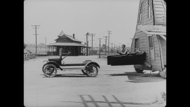 vídeos y material grabado en eventos de stock de 1920 man (buster keaton) nails the car seat to the house for easier towing, but when he starts the car, it takes off leaving the seat behind and nailed to the wall - rasgado
