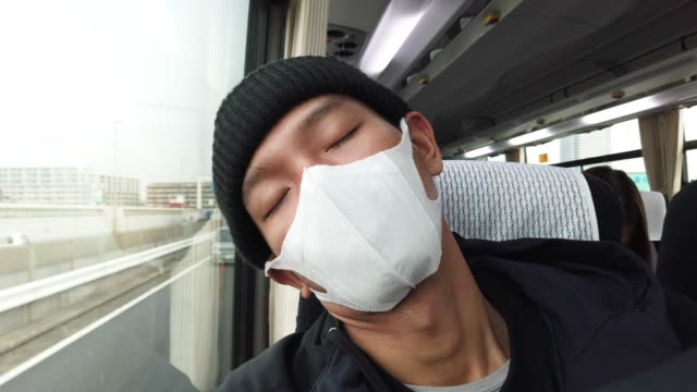 man nap on bus wearing a mask and beanie - smog stock videos & royalty-free footage