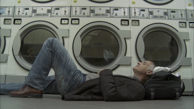 ms man napping on floor in laundromat / brussels, belgium - laundry stock videos & royalty-free footage
