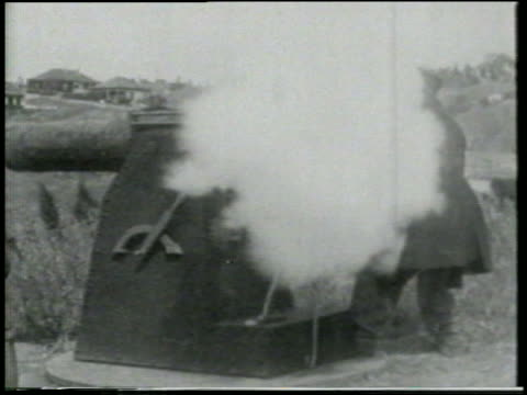 stockvideo's en b-roll-footage met b/w 1915 man (chester conklin) near grassy hills firing cannon / short - 1915