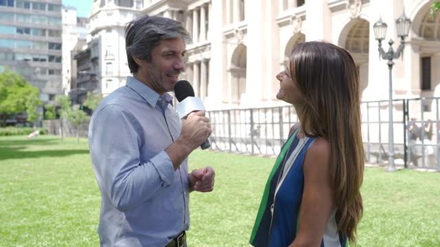 vídeos y material grabado en eventos de stock de hombre reportero de noticias entrevistando a la mujer en la calle - entrevista grabación