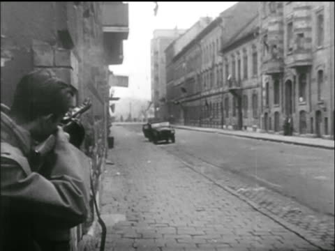 vídeos de stock e filmes b-roll de man next to building corner fires rifle / hungarian uprising - 1956