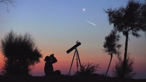 vidéos et rushes de un homme en observant le ciel nocturne - météore