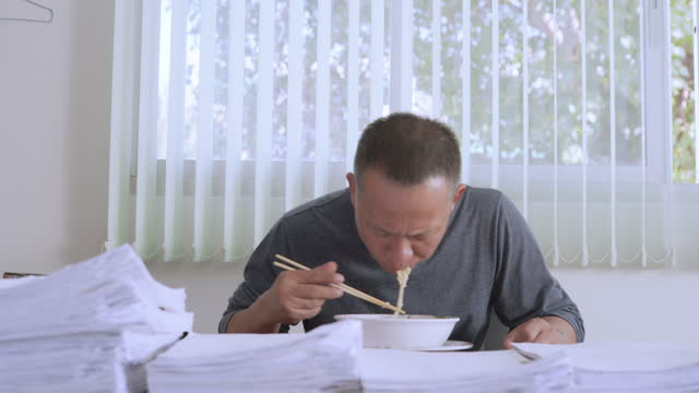 man of asian descent, aged 40-50 in casual attire eats noodles on a desk full of documents - file clerk stock videos & royalty-free footage