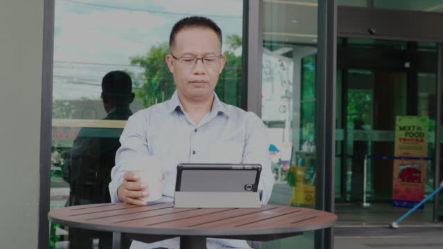 man of asian descent, aged 40-50, wear casual clothes sitting and drinking coffee and using a tablet at a coffee shop ,happiness means everything as inspiration concepts, - southeast asia stock videos & royalty-free footage