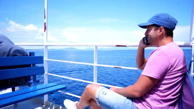 Man on a boat deck talking on the phone