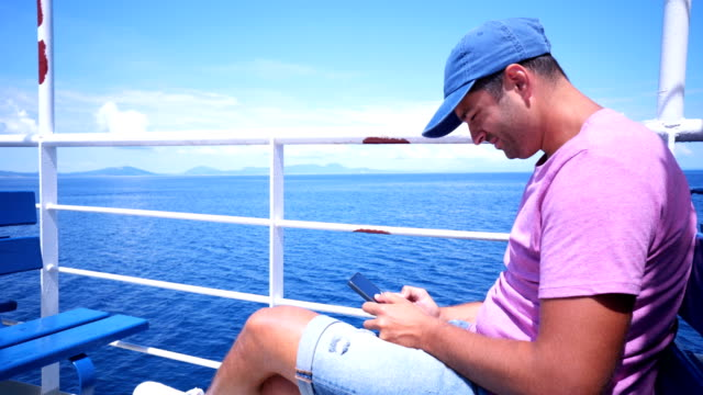 Man on a boat deck texting messages