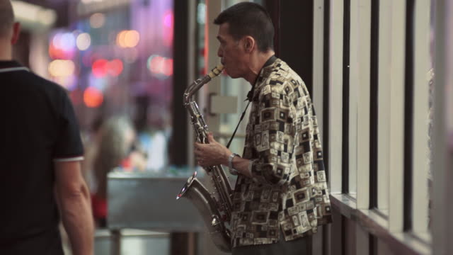 a man on a busy street corner playing the saxophone at night near time square - musician stock videos & royalty-free footage