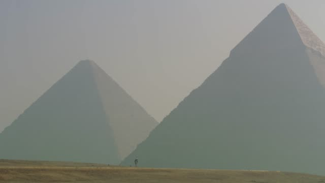 a man on a camel, dwarfed by the two main giza pyramids in egypt. - pyramid stock videos and b-roll footage