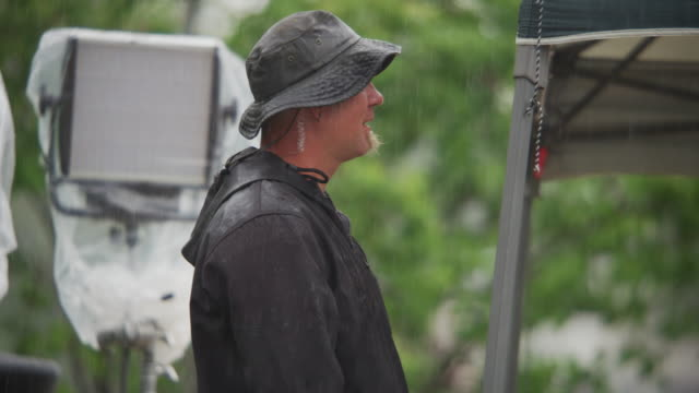 A man on a motion picture crew stands under a tent during a rainstorm with LED lighting fixtures in the background.