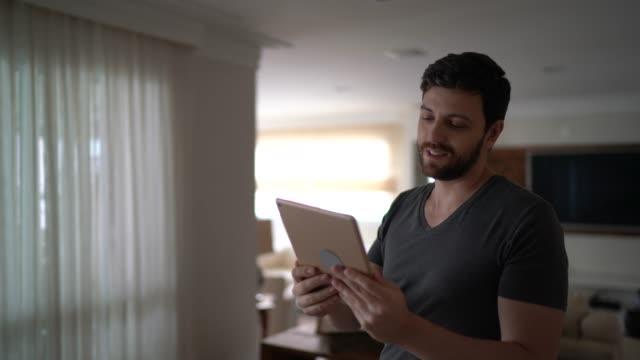 デジタルタブレット上のビデオ会議上の男 - 自宅で歩く - 人里離れた点の映像素材/bロール