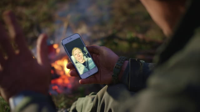 vídeos de stock e filmes b-roll de man on a videocall with his wife while sitting by the campfire - território selvagem