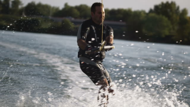 man on a wakeboard behind a boat - wakeboarding stock videos and b-roll footage