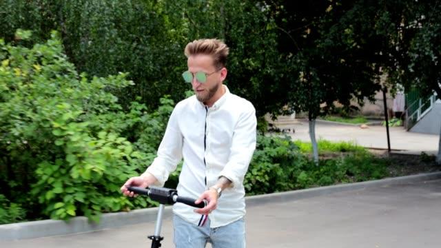 vidéos et rushes de un homme sur un scooter électrique. - scooter