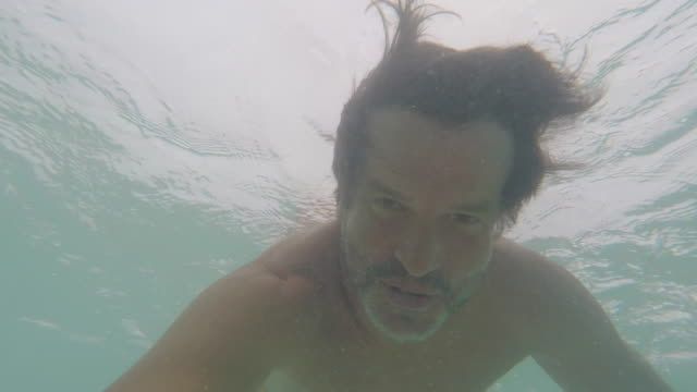 vidéos et rushes de man on and under the sea - south pacific ocean