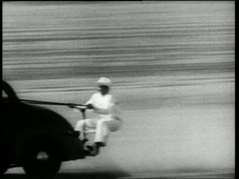 b/w 1950 pan man on back of speeding car landing on rear end on ground / crashing the movies - acrobazia video stock e b–roll