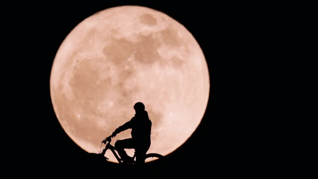 """man on bike silhouetted against rising super moon - """"bbc universal"""" stock videos & royalty-free footage"""