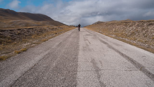 man on bycicle in campo imperatore - italy - mountain road stock videos & royalty-free footage