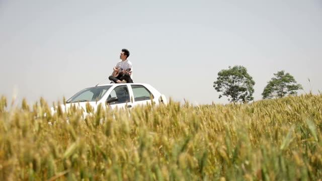 man on car playing guitar in the wheat fields - 胡坐点の映像素材/bロール