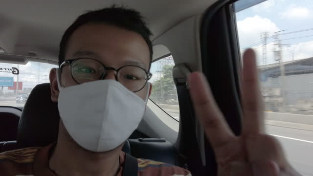man on car wearing a mask . smiling behind the mask - passenger seat stock videos & royalty-free footage