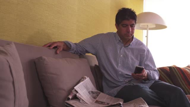 ms man on couch, checking newspaper, using tv remote / portland, oregon, united states - portland oregon点の映像素材/bロール
