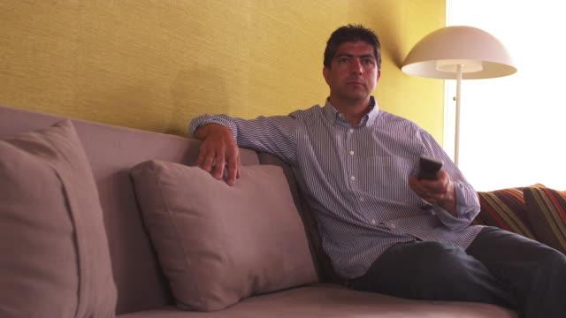 ms man on couch, using tv remote / portland, oregon, united states - portland oregon点の映像素材/bロール
