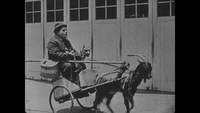 stockvideo's en b-roll-footage met 1918 man (buster keaton) on date falls off goat pulled wagon before another man (fatty arbuckle) comes along and does the same thing - paardenkar