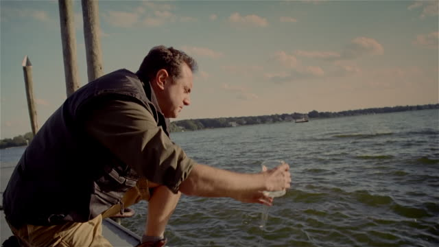 Man on dock collecting water sample in test tube / looking at sample