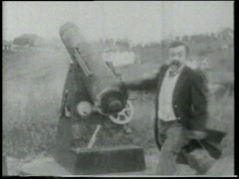 stockvideo's en b-roll-footage met b/w 1915 man (chester conklin) on grassy hill aiming large cannon with cane / feature - 1915