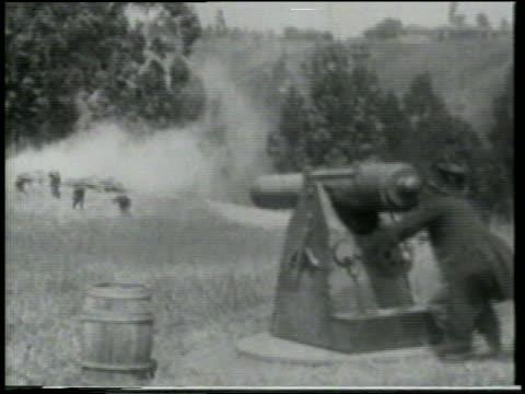 b/w 1915 man on grassy hill firing cannon at approaching running keystone kops / feature - 1915年点の映像素材/bロール