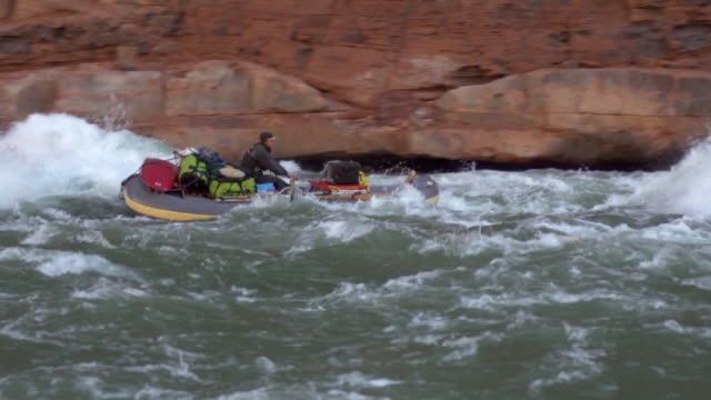 WS PAN Man on gray boat floating down rapidly with red cliffs in background / Grand Canyon, Arizona, USA