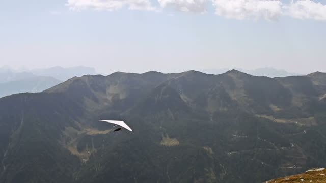 WS TS Man on hand glider taking of from mountain cliff on Italian Alps / Brunico, Italy