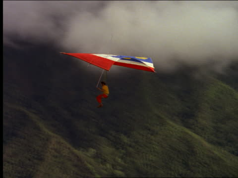 aerial man on hang gliding over mountainous coastline - hang gliding stock videos and b-roll footage