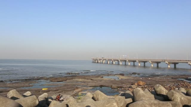 Man on his back stretches his leg on the promenade beside the Bandra Worli Sea Link A man washes his clothes on the breakwater beside the Bandra...