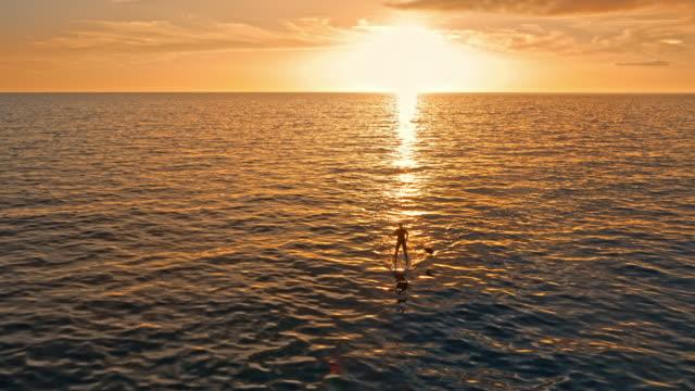 Homme aérienne sur son SUP en mer au soleil couchant doré