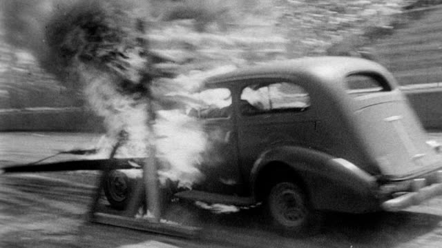 man on hood of a car as driver of car crashes through a framework of fire hollywood stuntmen display skills on june 05, 1951 in hollywood, california - stunt person stock videos & royalty-free footage