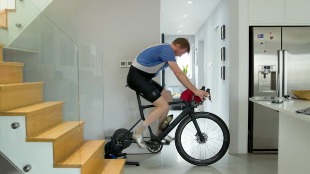 man on indoor bike turbo trainer. he mops his brow - active lifestyle stock videos & royalty-free footage