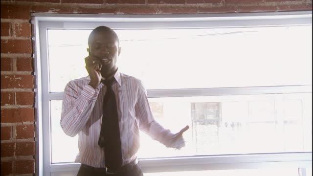 vídeos de stock e filmes b-roll de ms, man on mobile phone in front of window, los angeles, california, usa - camisa e gravata