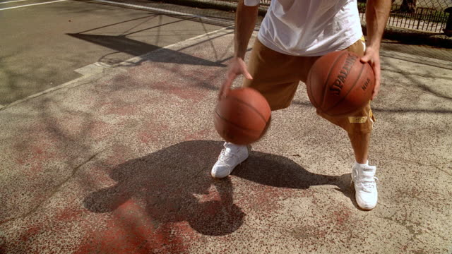 ms man on morningside park basketball court dribbling and juggling two basketballs/ harlem, new york  - juggling stock videos & royalty-free footage