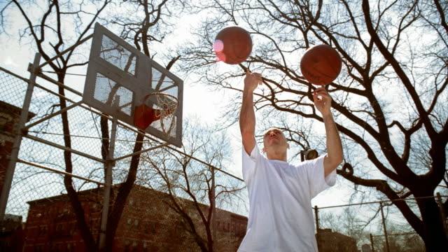 vídeos y material grabado en eventos de stock de ms man on morningside park basketball court holding one basketball in each hand/ man throwing balls in air and spinning them on the index finger of each hand/ harlem, new york  - camiseta