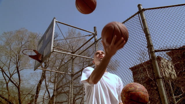 LA MS Man on Morningside Park basketball court juggling two basketballs across his chest/ Harlem, New York