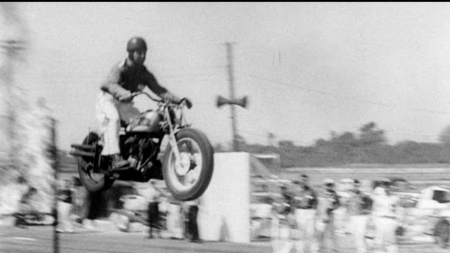 man on motorcycle drives up ramp and jumps through fire Hollywood stuntmen display skills on June 05 1951 in Hollywood California