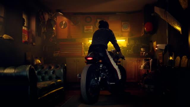 man on motorcycle in his workshop - laboratorio riparazioni video stock e b–roll