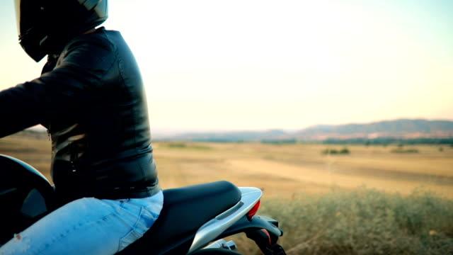 man on motorcycle in sunset - casco da motociclista video stock e b–roll
